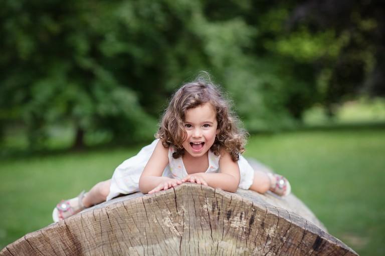 Focení v přírodě holčička leží na kmenu stromu